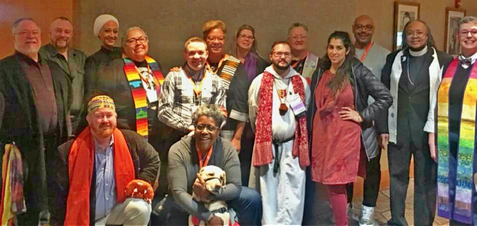 15 members of the 2018 spiritual care team, smiling; people of many ages, races, and religious/nonreligious dress, plus Sandy the chaplain dog